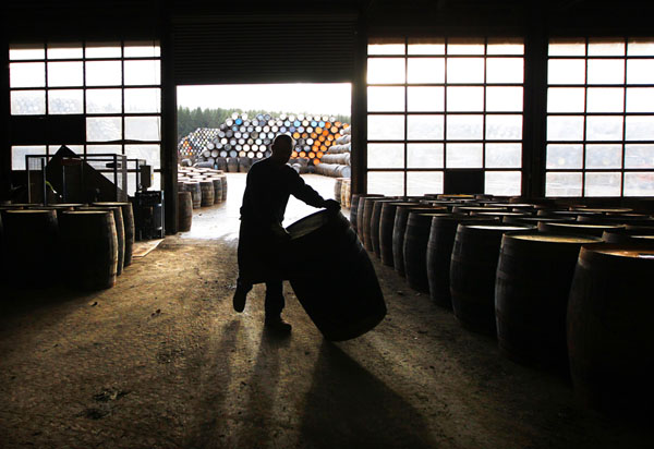 A cooper rolls a scotch whisky cask along the floor before starting the process to repair it at the Speyside Cooperage in Craigellachie